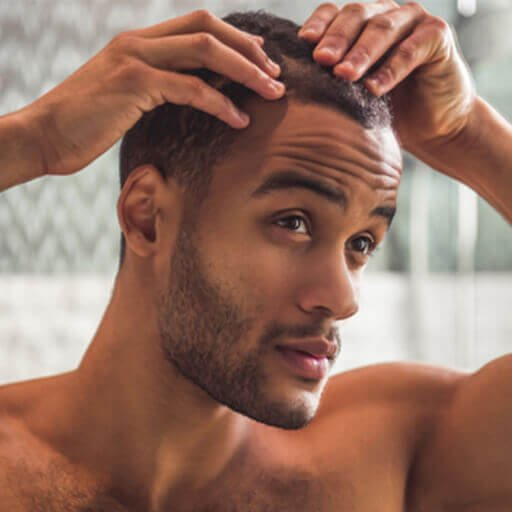 A man checking his scalp for symptoms of hair loss